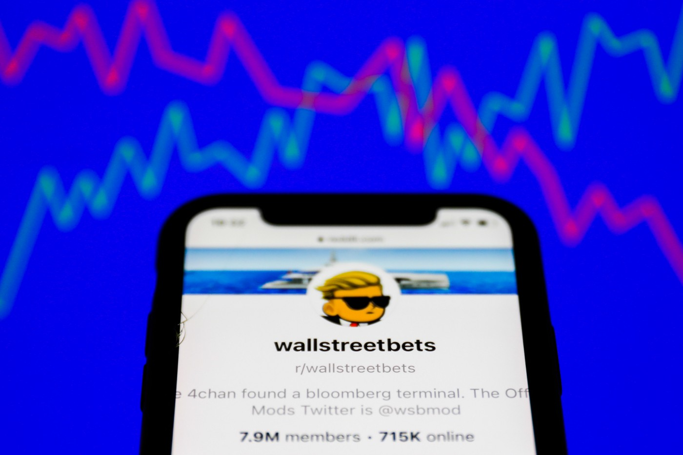 WallStreetBets forum on the Reddit displayed on a phone screen and a illustrative stock chart in the background