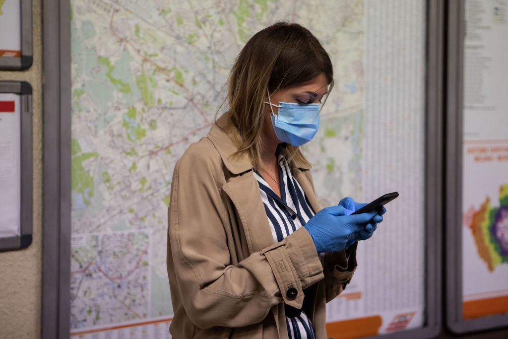 A photo of a woman wearing a mask and gloves on her phone waiting for a train.
