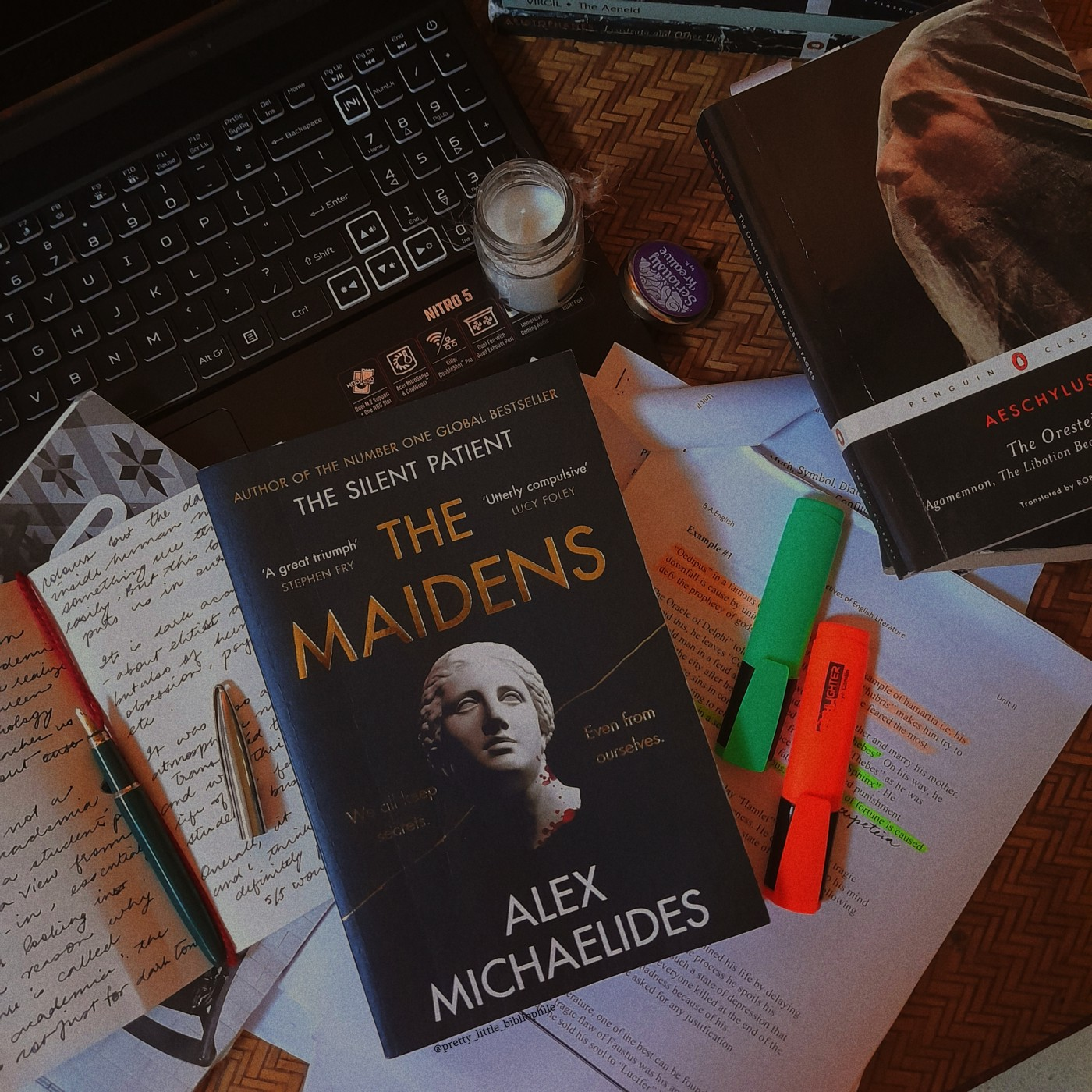 'The Maidens' on a cluttered desk, with an open notebook, a laptop, and other books around. The cover is black with gold writing and a plaster bust in the centre.