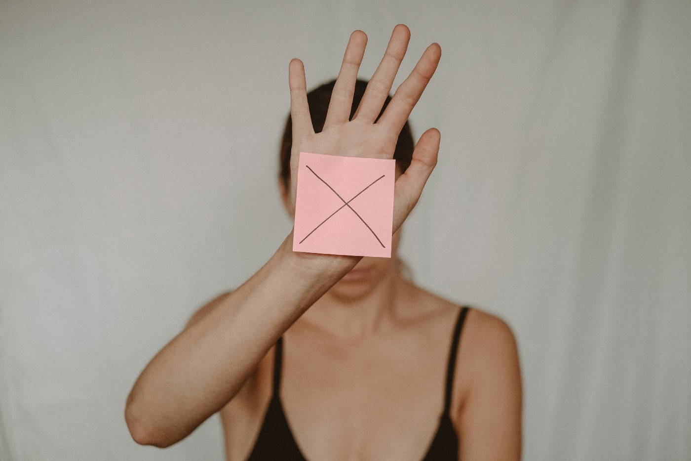 A lady showing a postit marked X