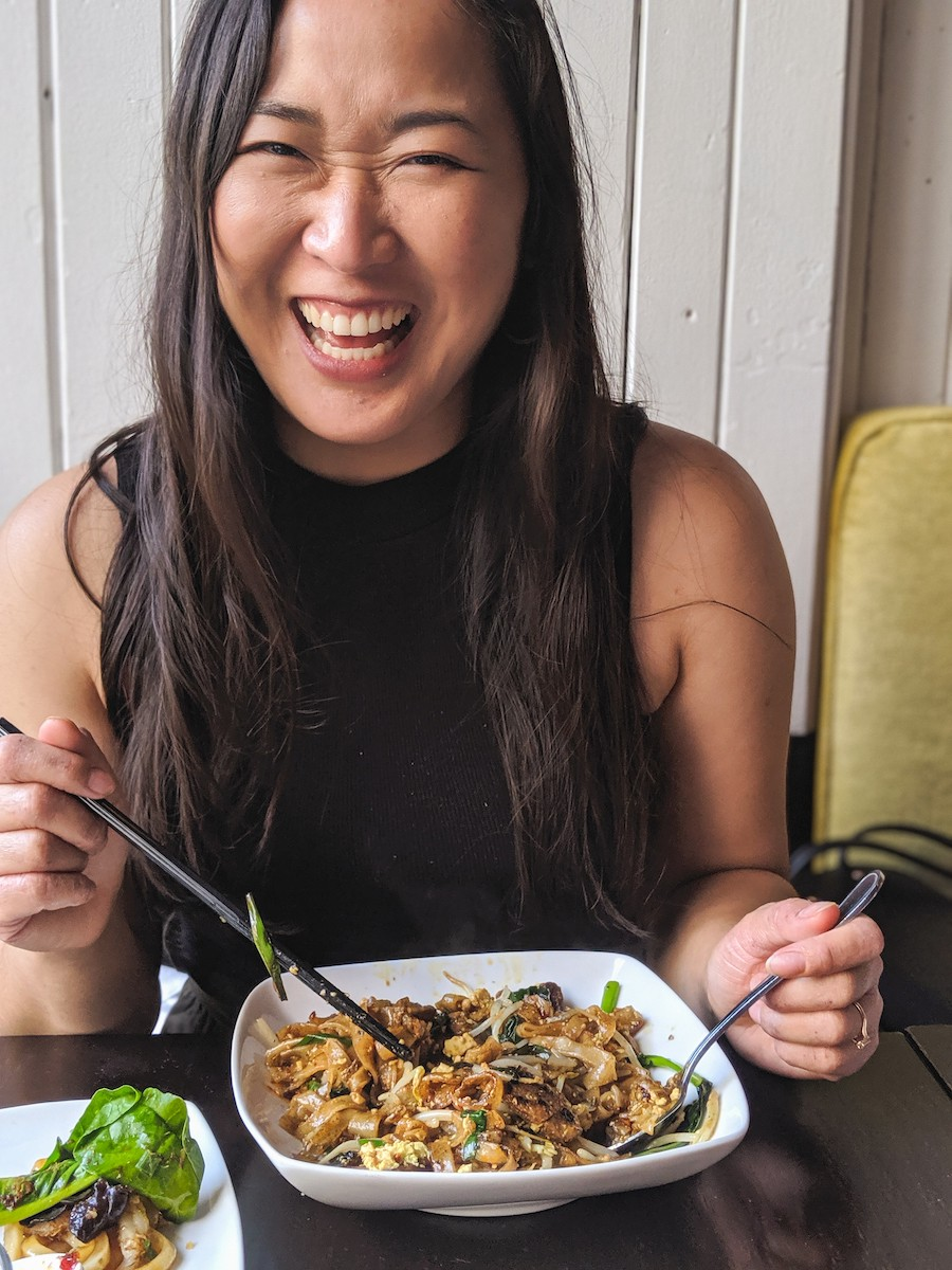 Lisa Le smiles while posing with a plate of delicious noodles.