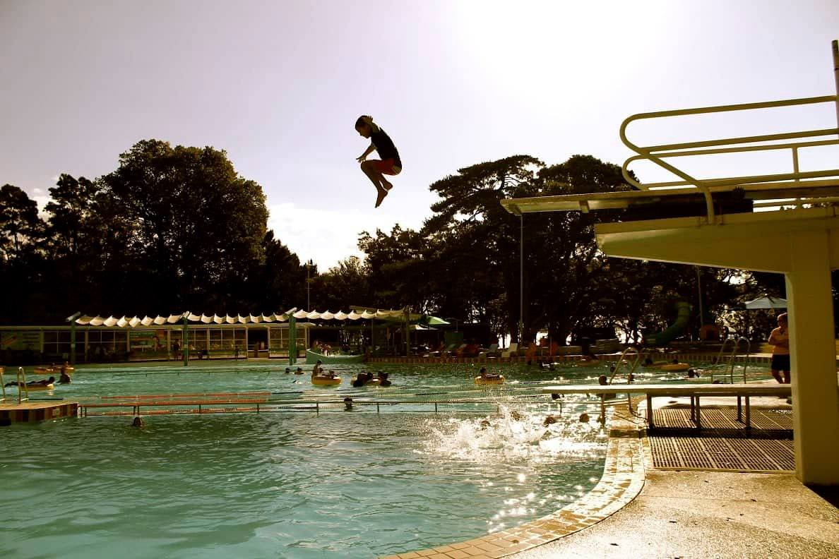 Young child jumps off diving platform into swimming pool, sun shines from behind
