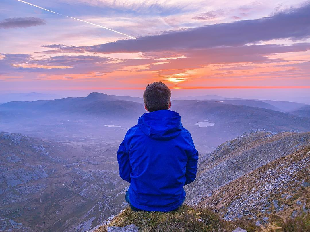 A guy sitting on the cliff of a mountain watching the clouds and a most beautiful sunset.