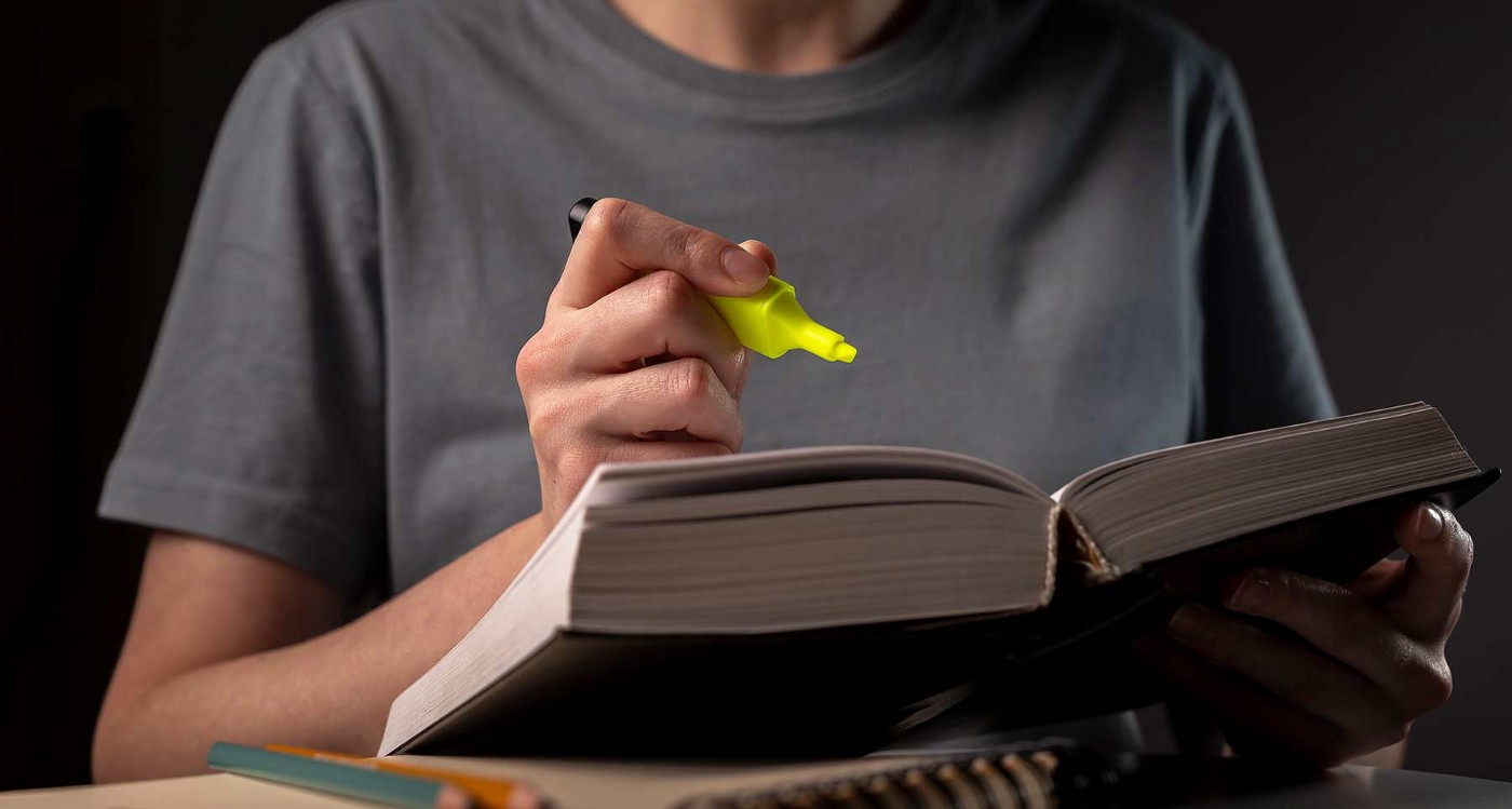 A hand holds a yellow highlighter over an open book.