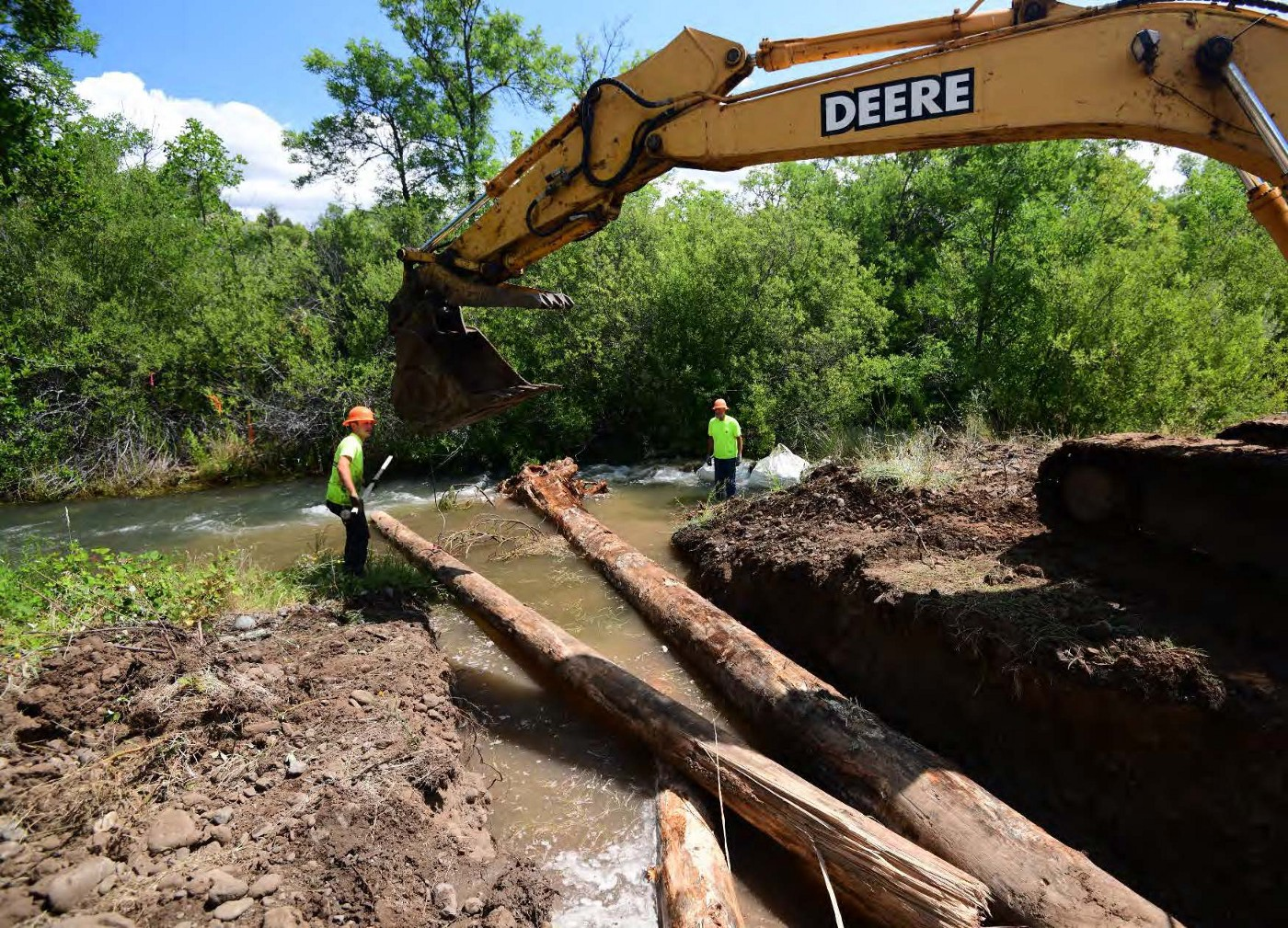 A large excavator puts big pieces of woody debris into the river