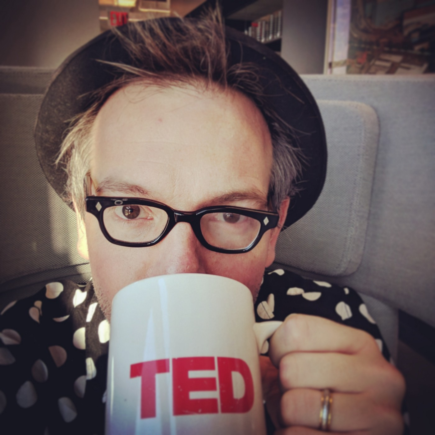 Selfie of author wearing vintage spectacles, bowler and a black-and-white polka dot shirt sips coffee from a TED mug