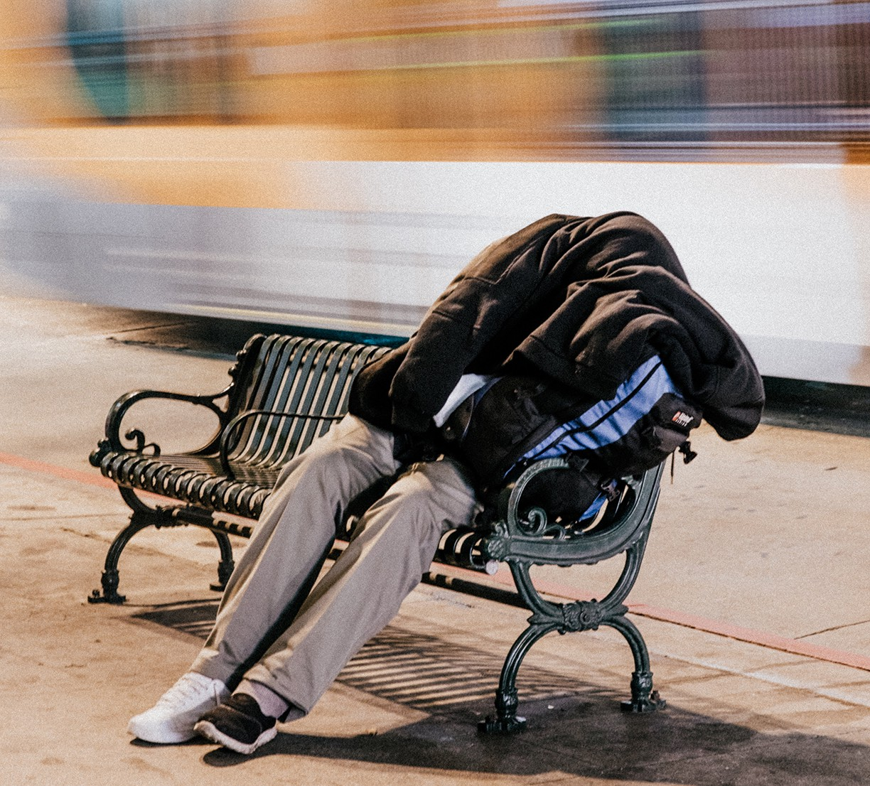 A homeless person sits on a bench, covered by a jacket.