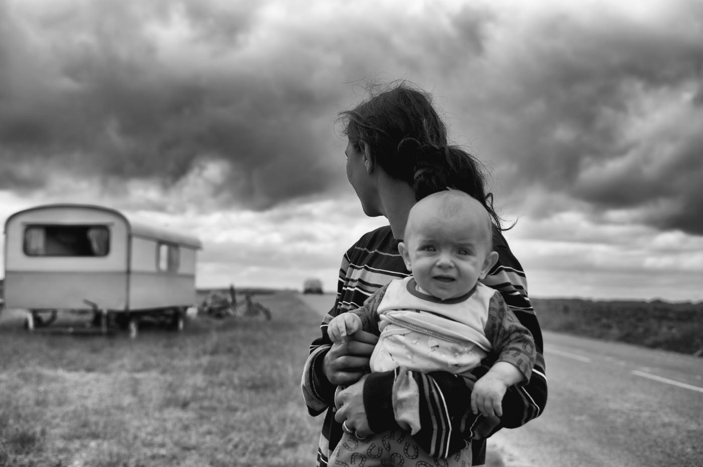 Baby looking at the camera while woman holding it looks behind her toward a trailer.