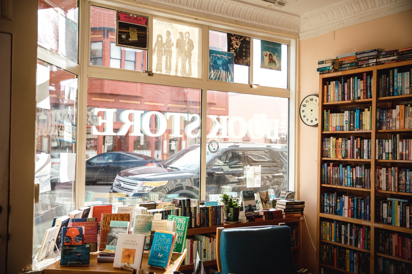 A view from inside a bookstore out the front window into the daylit street beyond, with tables and shelves full of book in the foreground.
