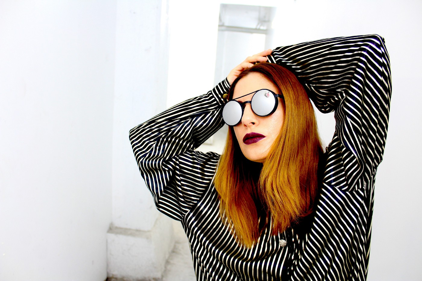 A woman in round-framed sunglasses and a striped shirt strikes a pose with her hands on her head.