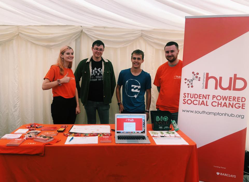 From left to right, Holly, Jordan, Jack and Tom are at the volunteering fayre, behind a table with leaflets on.