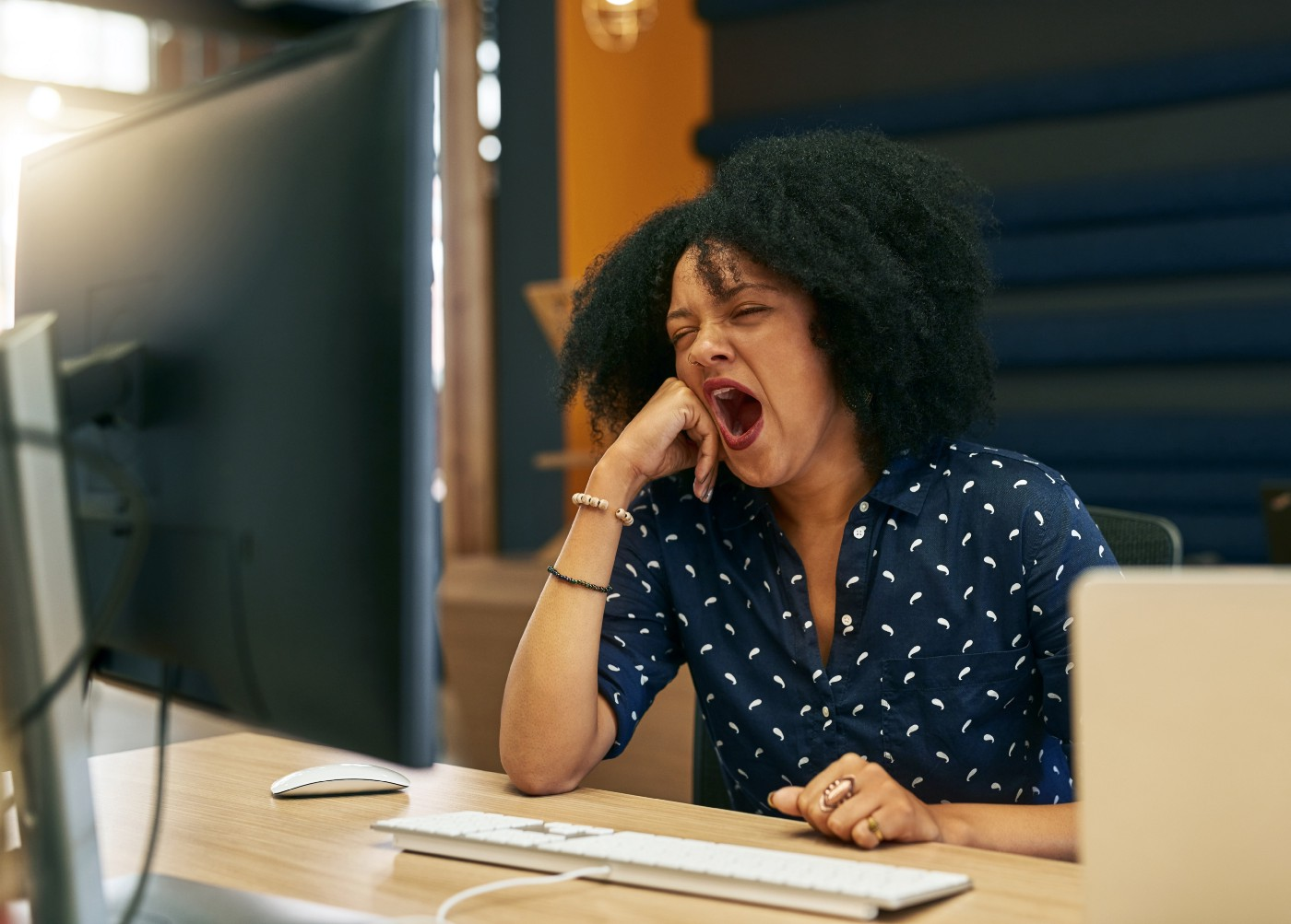 A young woman yawning at her desk while looking at her computer.