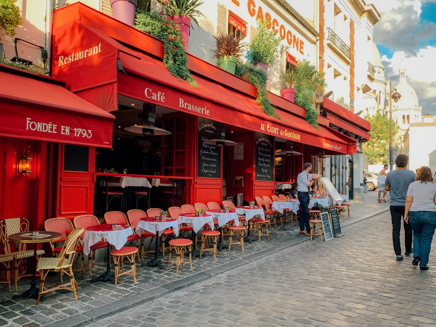 A cafe in Paris with a bright-red awning and exterior, seen from the street.