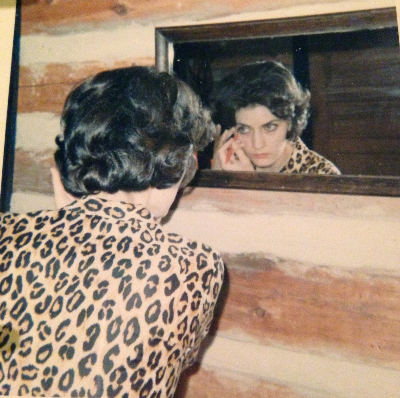 A young woman in a leopard-print top looks into a mirror as she applies makeup.