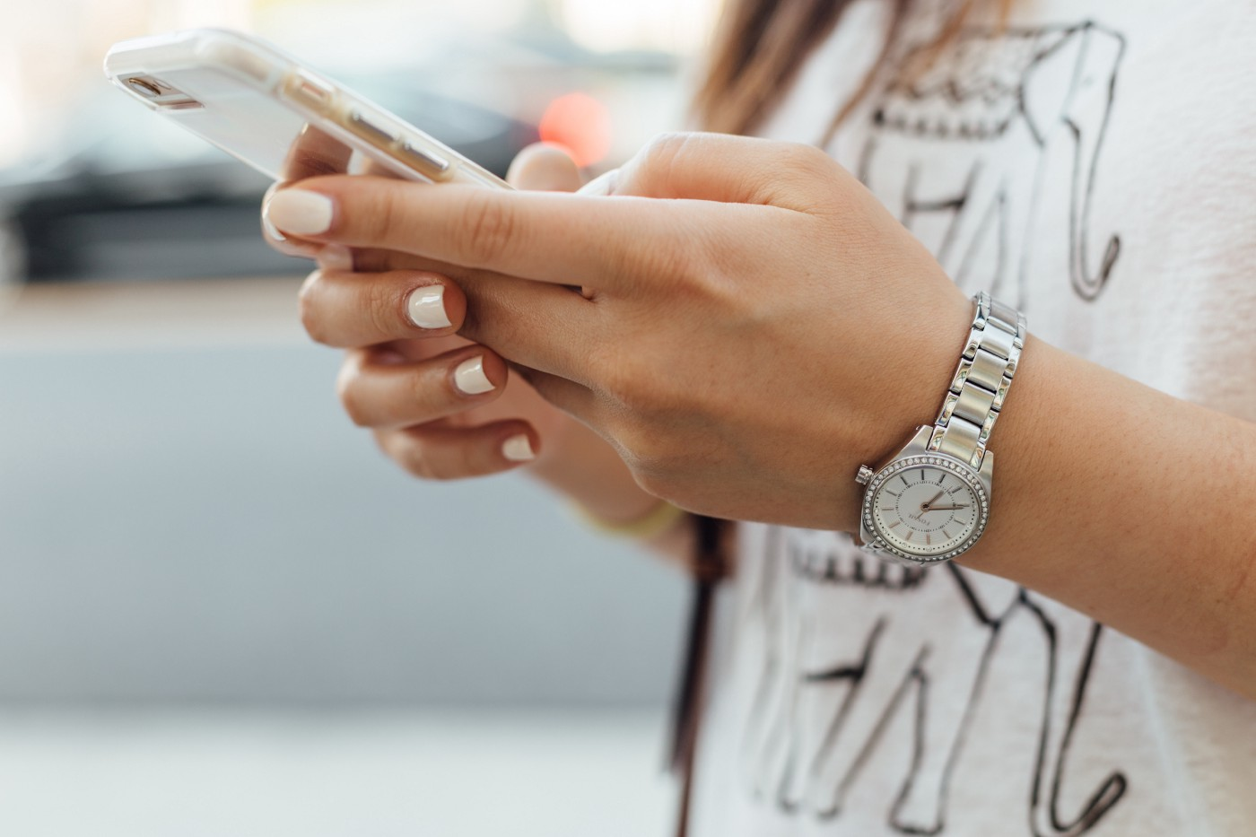 A young woman looking at a phone in her hands.