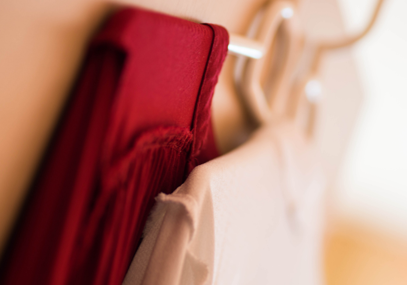 A red garment and a white garment hang against a wall.
