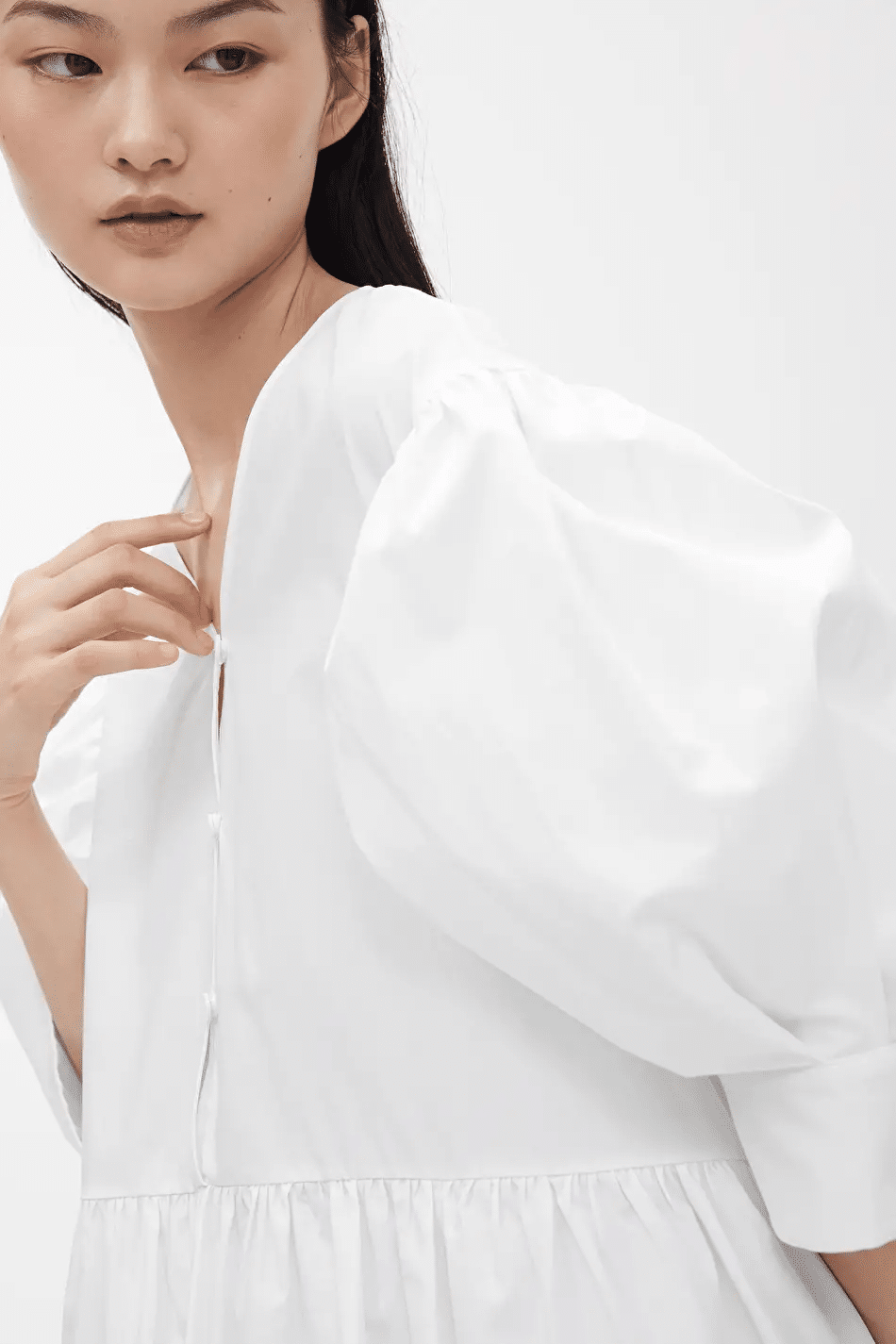 Model poses in white puff-sleeved blouse