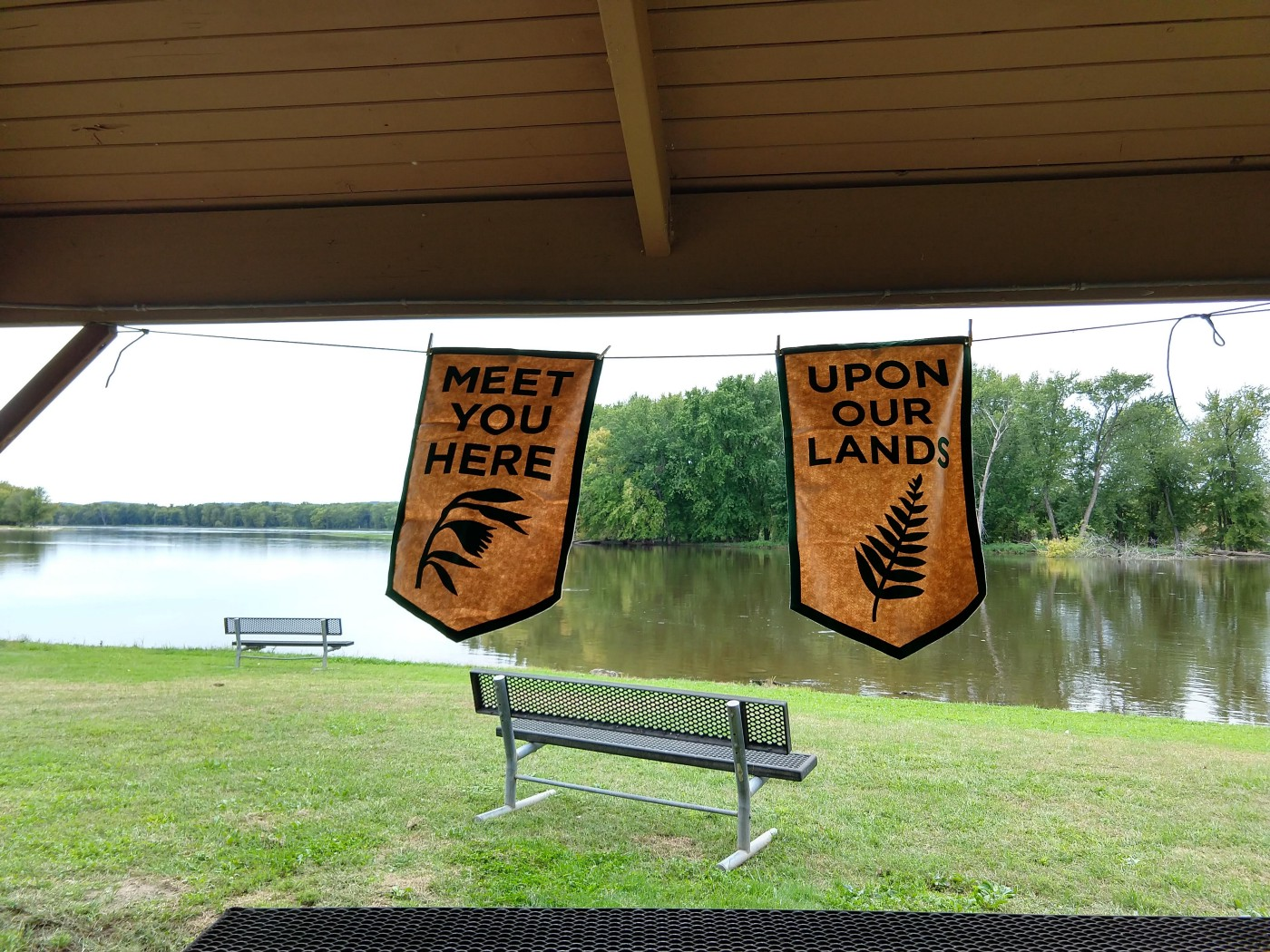 """Two banners reading """"Meet you here"""" and """"Upon our lands"""" in picnic shelter near river."""