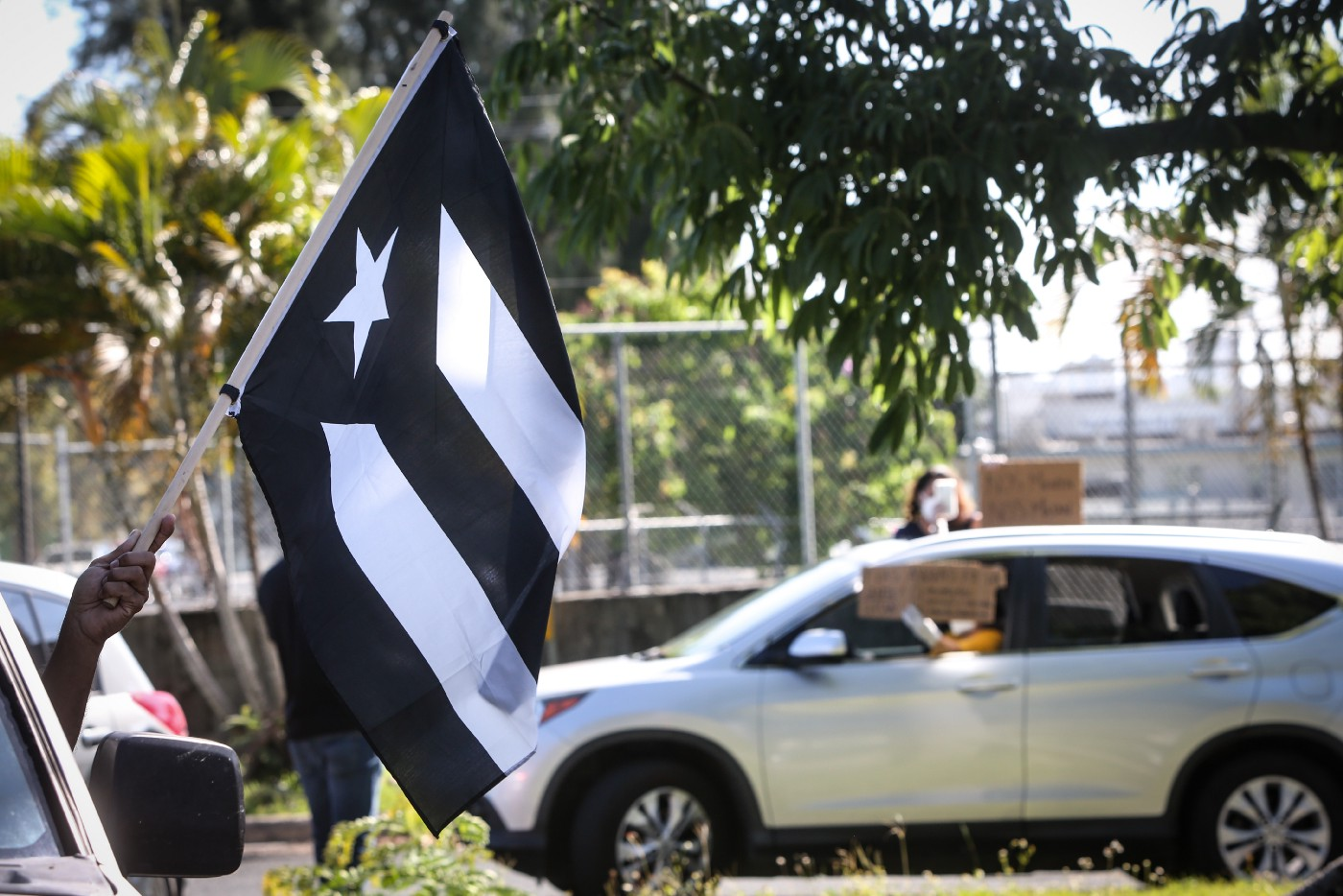 Demonstrators waved a Puerto Rican black flag in a protest calling for more Covid-19 tests to be conducted.