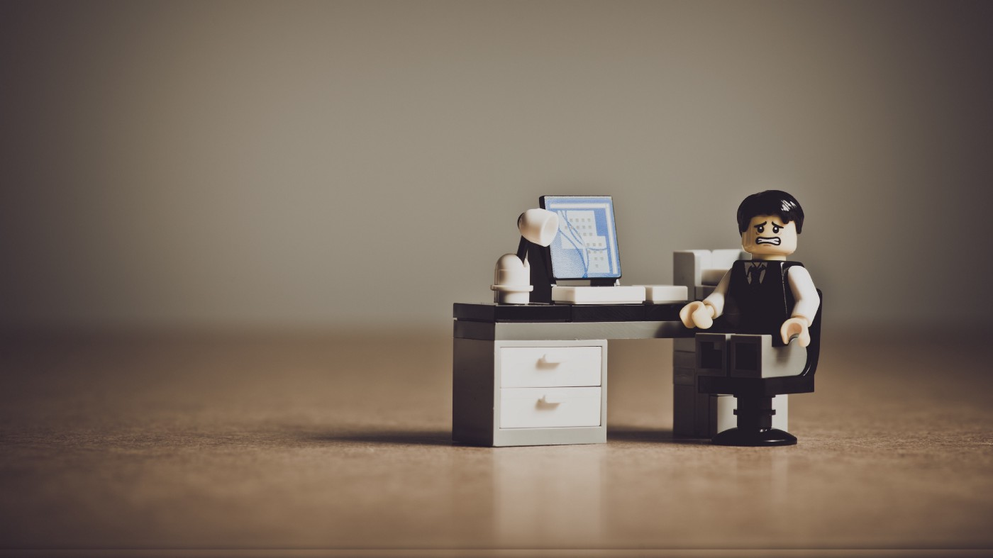 Image depicting a stressed out LEGO man sitting at his desk