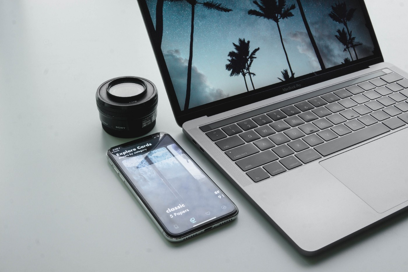 Phone, camera lens and laptop on table