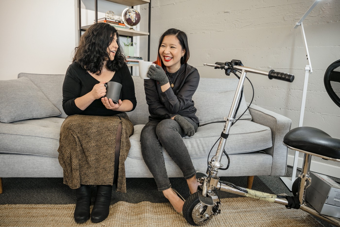 Two disabled women chat on a couch, both holding coffee mugs. An electric lightweight mobility scooter rests nearby.