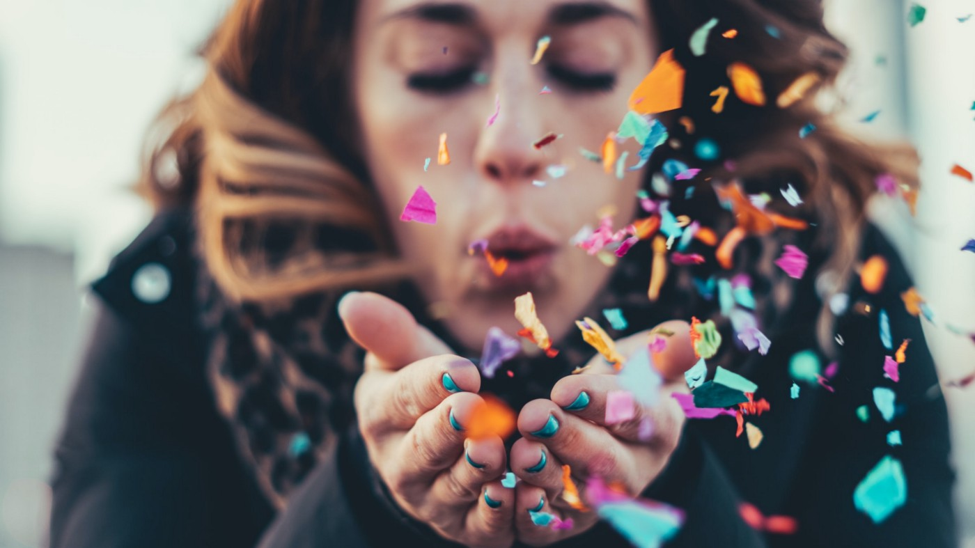 Woman blowing colorful confetti out of her hands.
