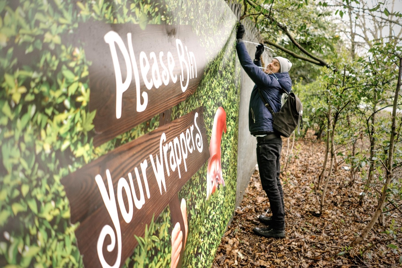 The image shows a tall fence covered by a banner in a wooded area. The banner has a green leafy background, a sign reading 'Please bin your wrappers' and a gnome's head pokes out from the foliage. Rob is standing at the end of the banner holding cable ties and grinning at the camera.