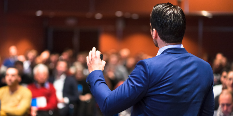 A man giving a speech to an audience for my article on the 5 Habits of an Insanely Good Speaker