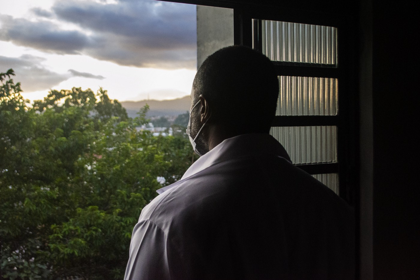 A photo from the back of a black man wearing a face mask looking out his window.