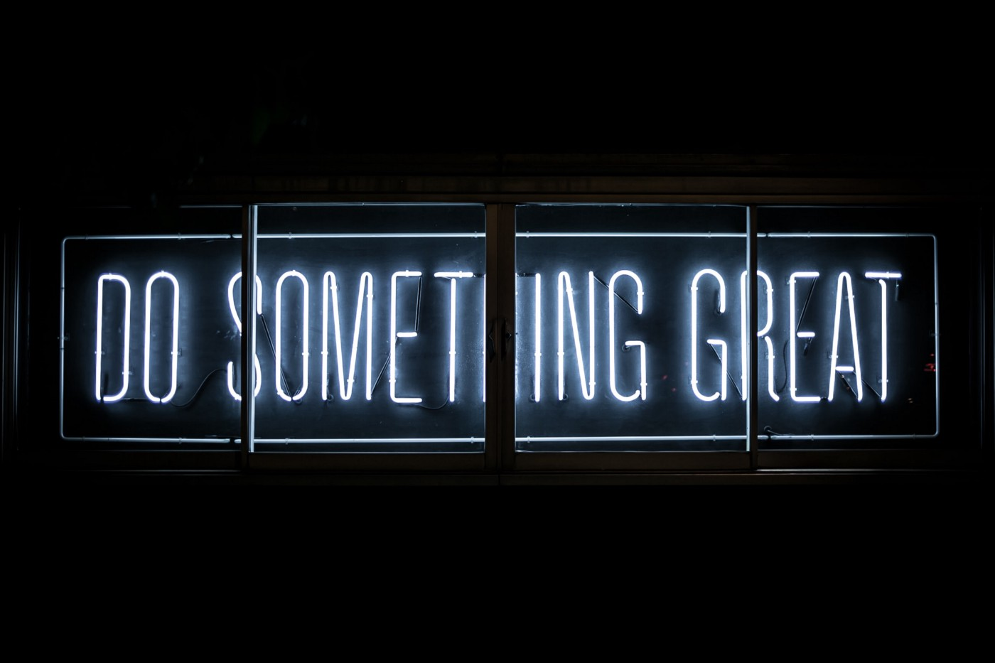 "Neon sign lit up with ""Do Something Great"" against a black backdrop."