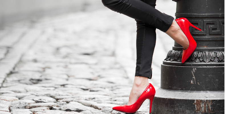 Woman with red high heels standing on a cobblestone street, for my article on the 7 Types of Sex Work You Didn't Know Existed