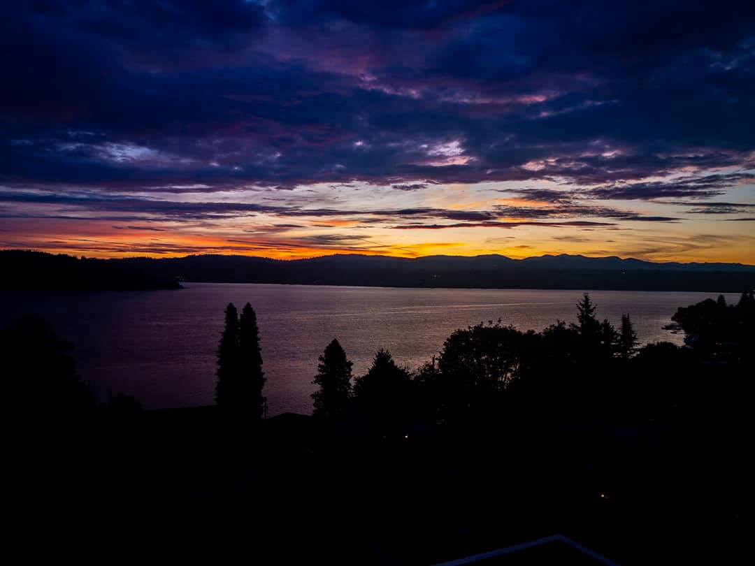 Sun rises over Lake Washington with gold and orange between black and gray of the water and land and the purple blue sky.