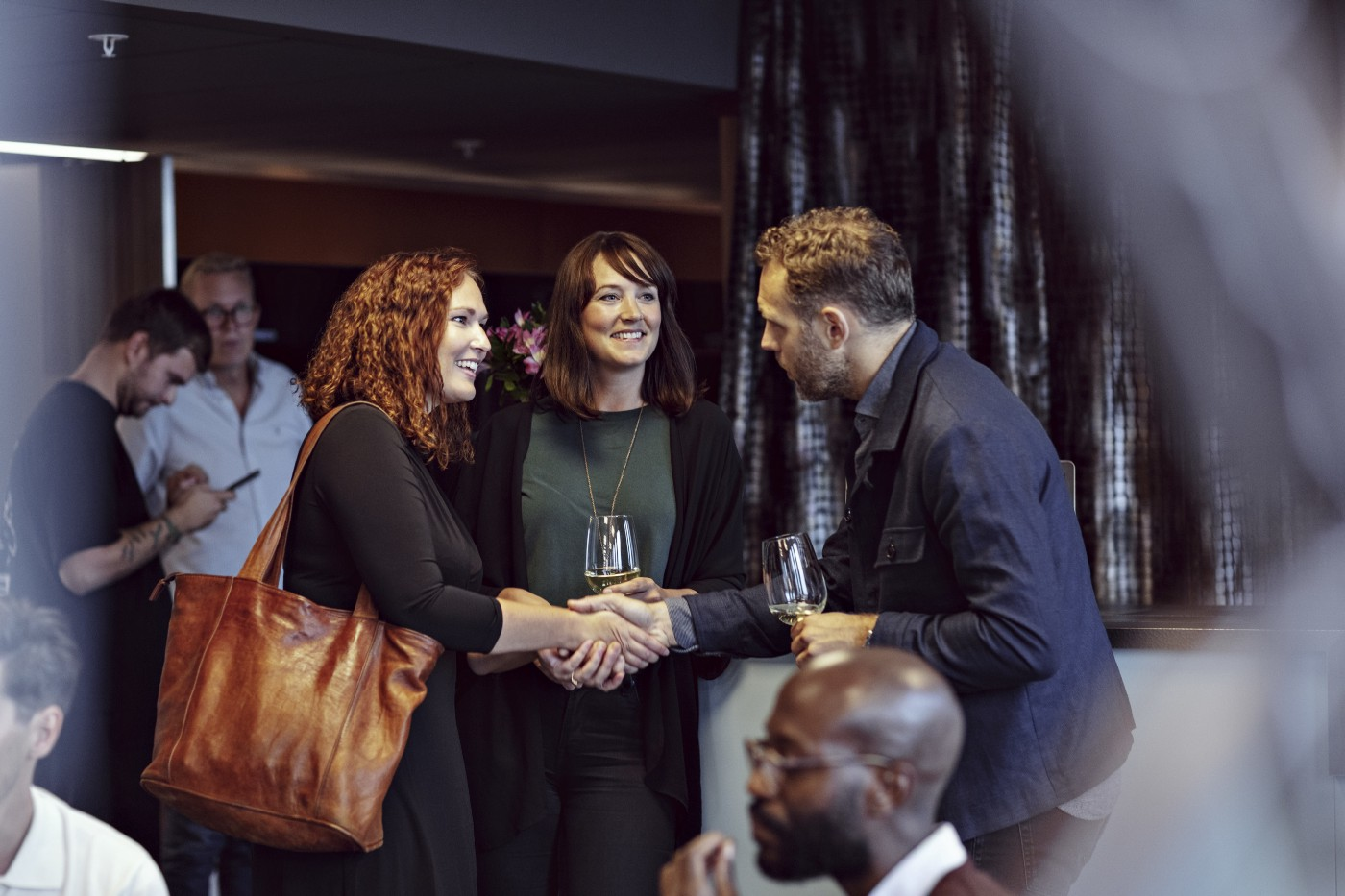 Business executives doing handshake while greeting during office party at conference