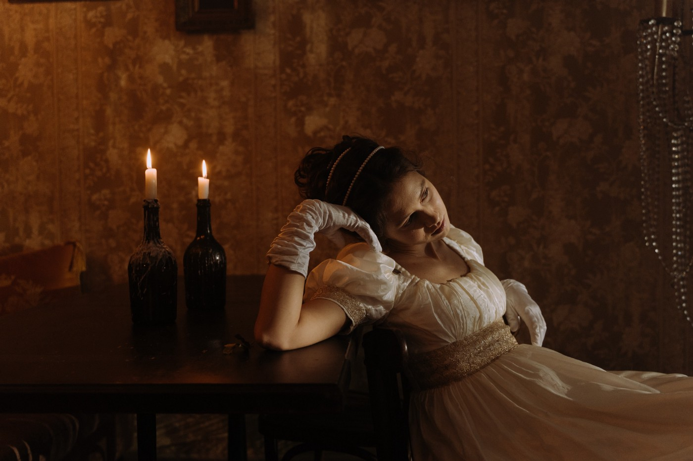 Woman in period costume leaning against a table with candles in bottles