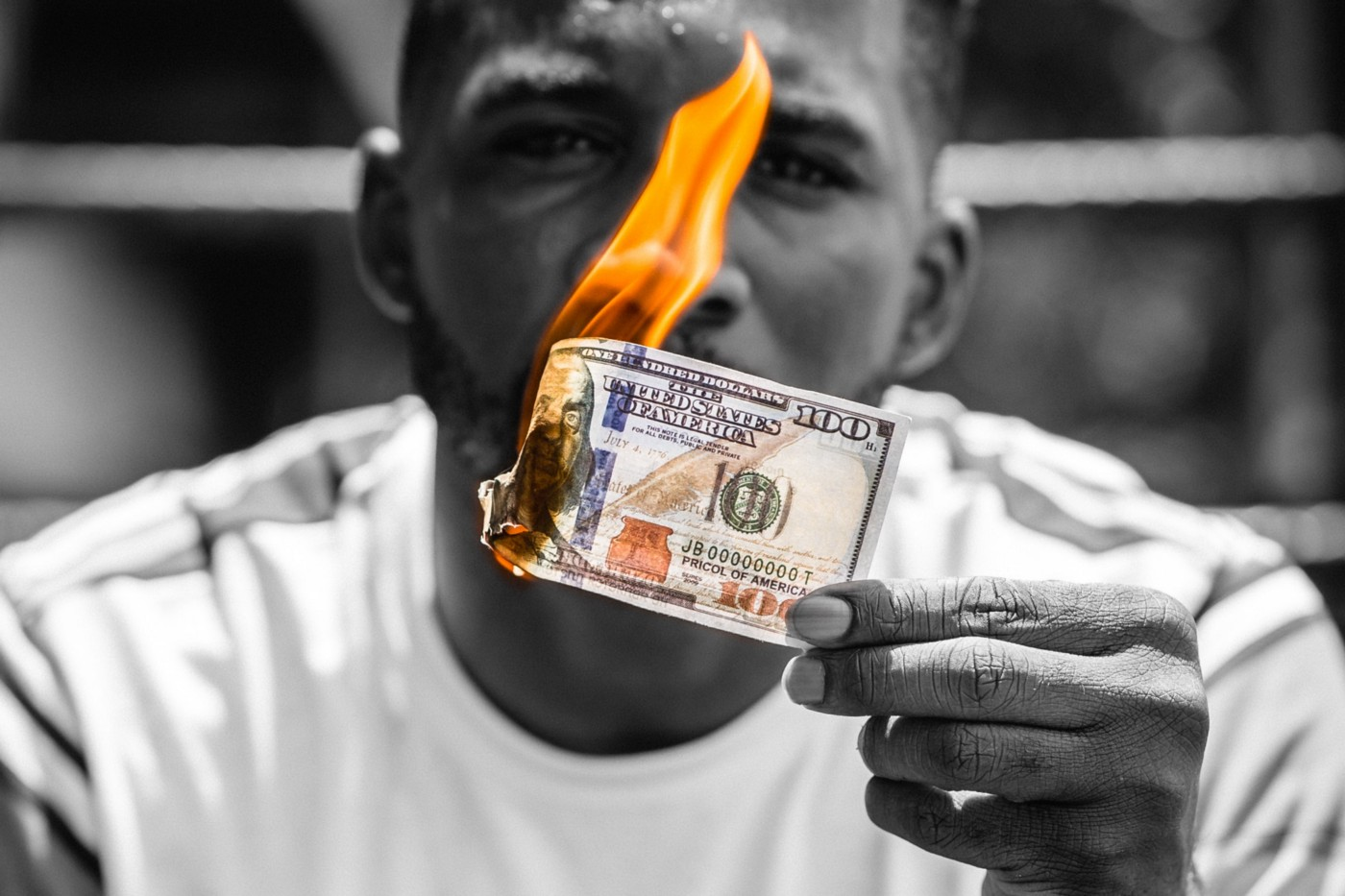 Man holding burning cash money