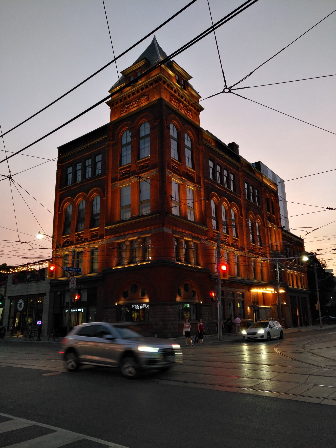 A Romanesque Revival style building at dusk at a major intersection with cars passing through.