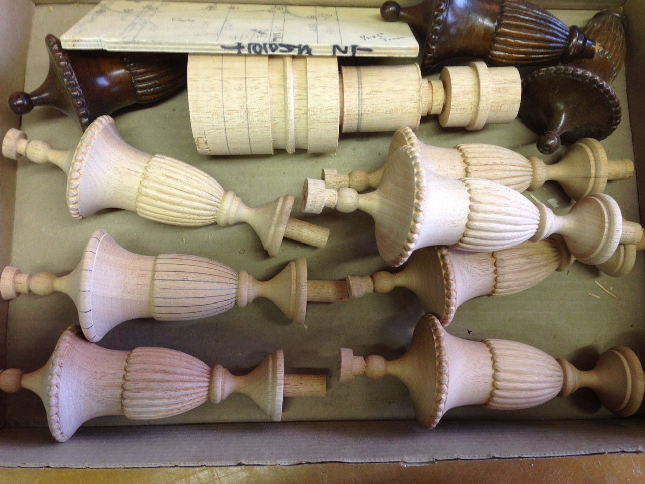 Finials for furniture piece, broken original pieces as well as work-in-process and new replacements ready for finishing.