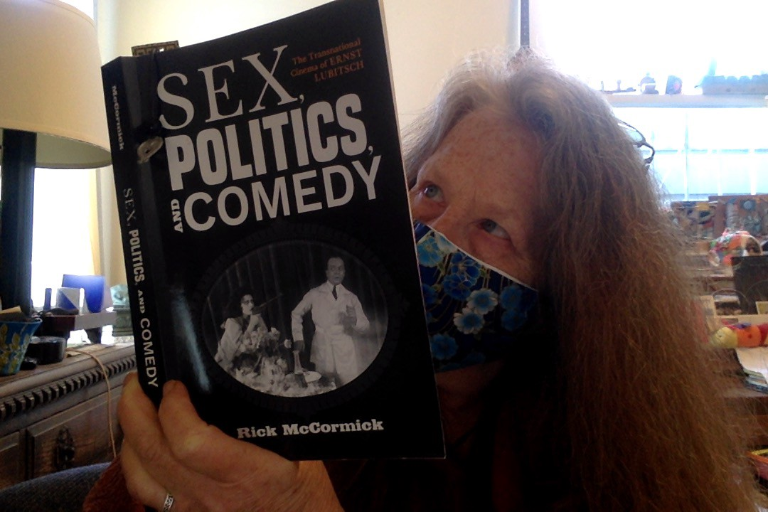 Wearing a mask, the author reads _Sex, Politics, And Comedy_.
