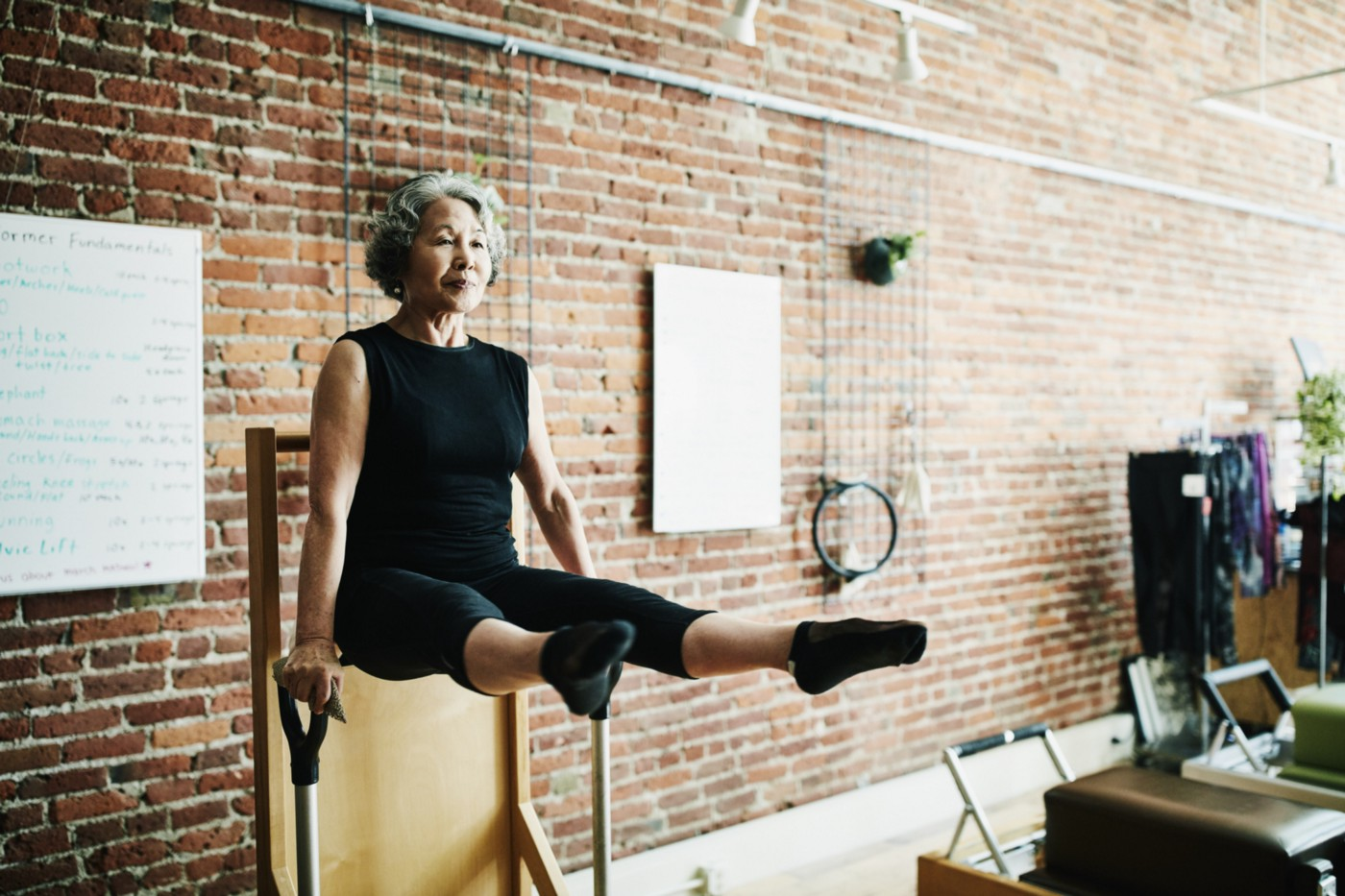Mature woman doing arm press on high-low pilates chair in fitness studio.