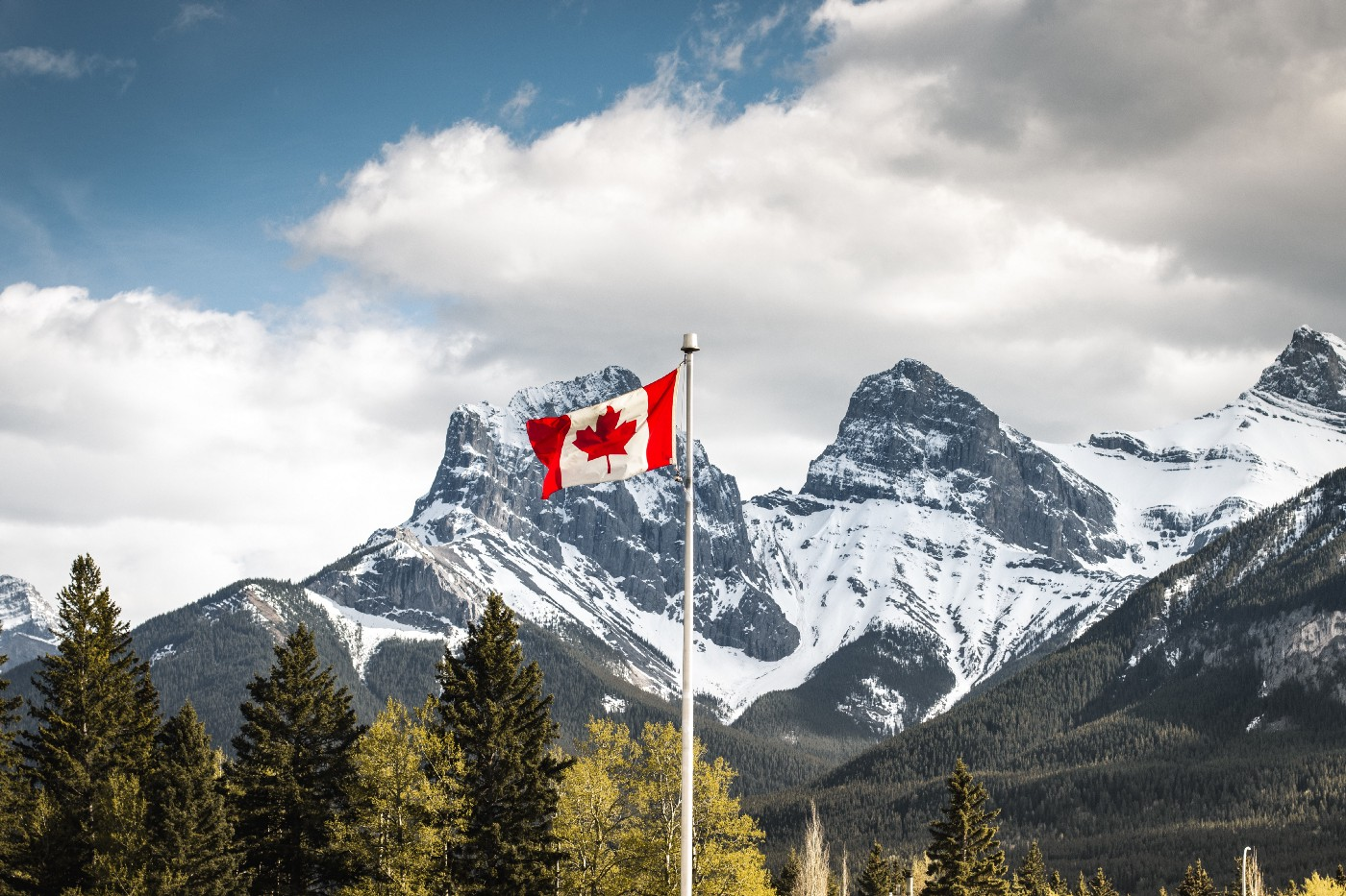 Canada Canmore, Alberta. Canadian Flag with Three Sisters in the Background. Photo and text by Igor Kyryliuk on Unsplash