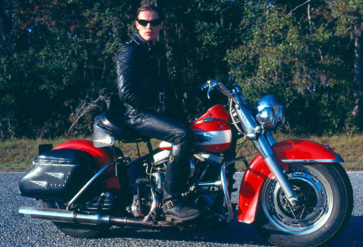 Willem Dafoe sits on an vintage motorcycle.