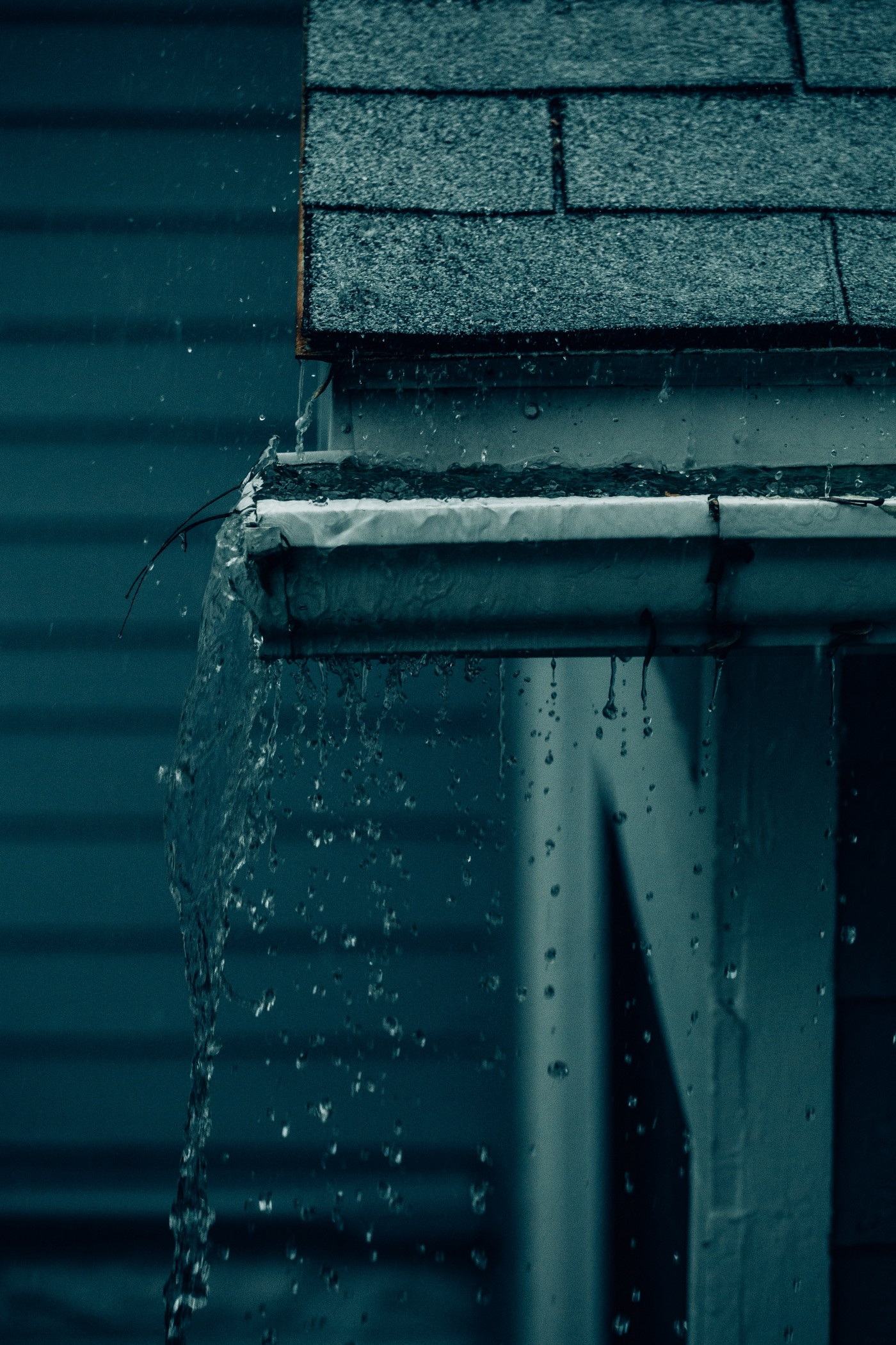 Rain falling on a rooftop. The rain runs into a gutter which is overflowing with water.