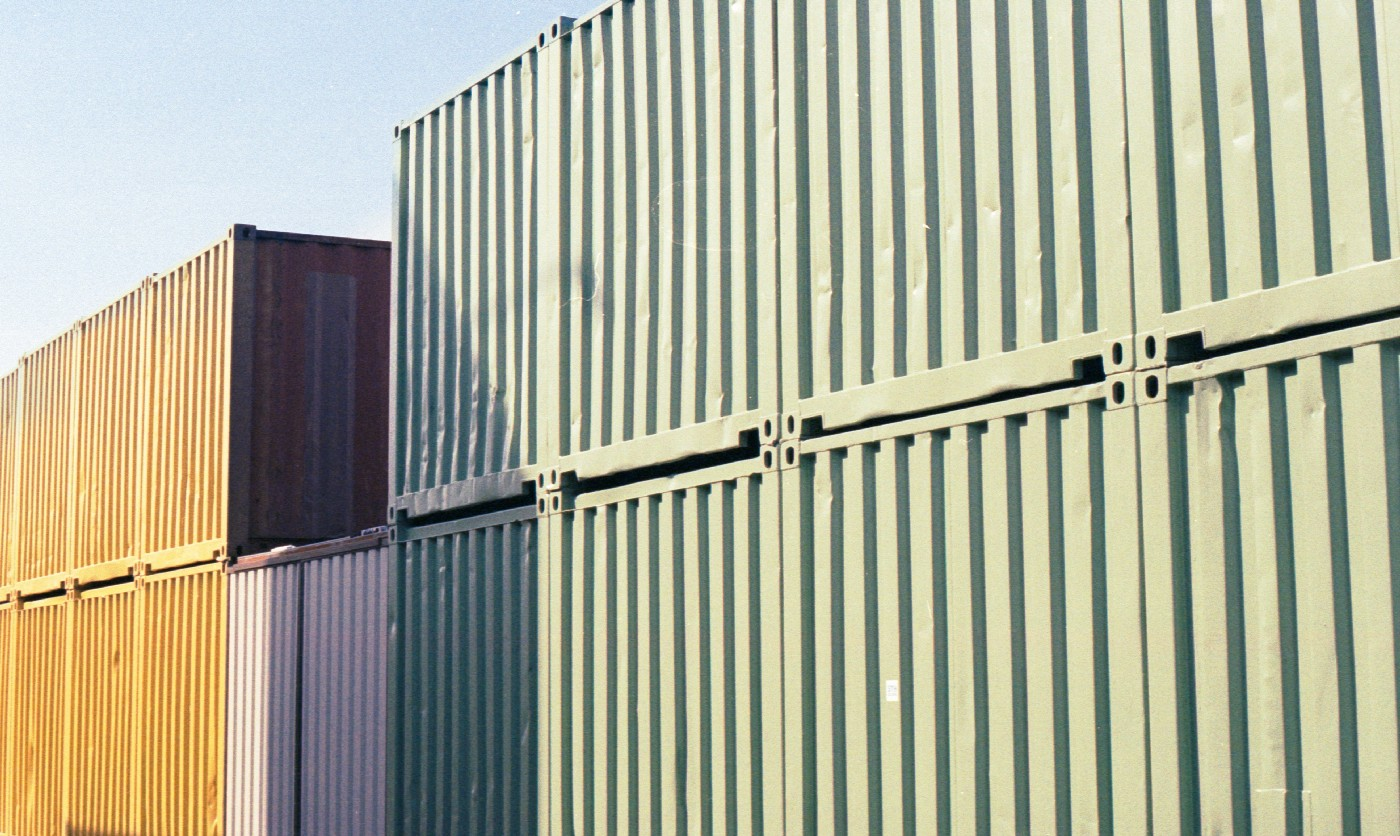 Two shipping containers on top of one another sit in the sun next to another pair of shipping containers.