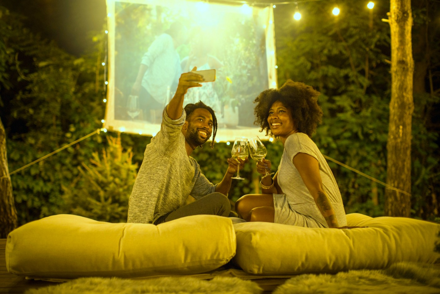 A Black couple take a selfie in their backyard, where they've set up a projector screen to watch a movie with hanging lights.