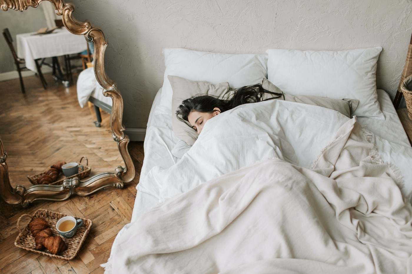 An individual covered in white blankets still in bed