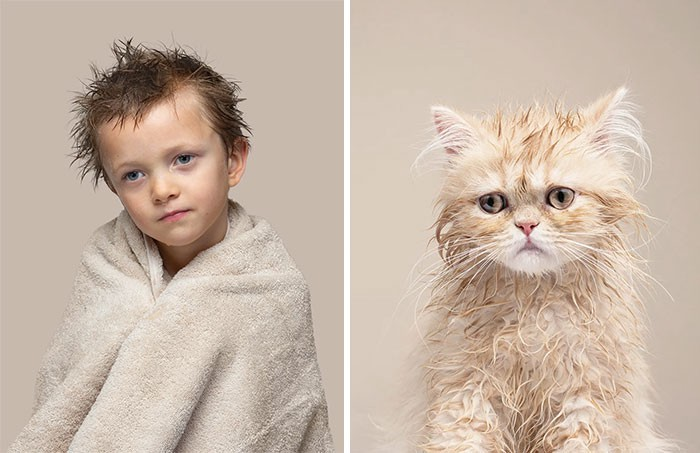 A kid just out of the shower holds a towel around his shoulders, next to a slightly damp kitten who isn't happy about a bath