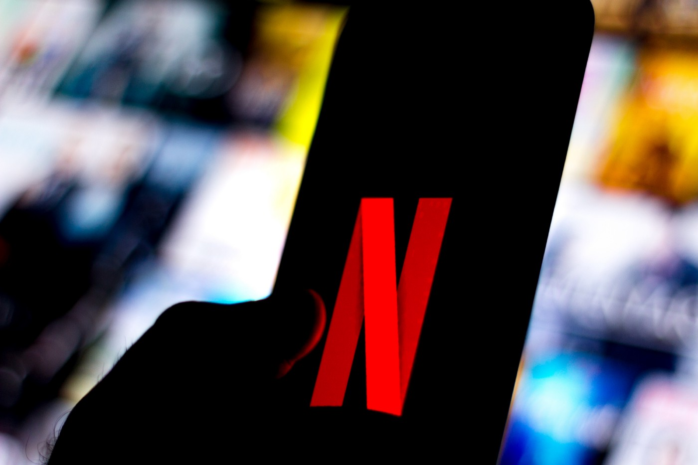 The Netflix logo is shown on a smartphone against a backdrop of blurred out Netflix show titles.