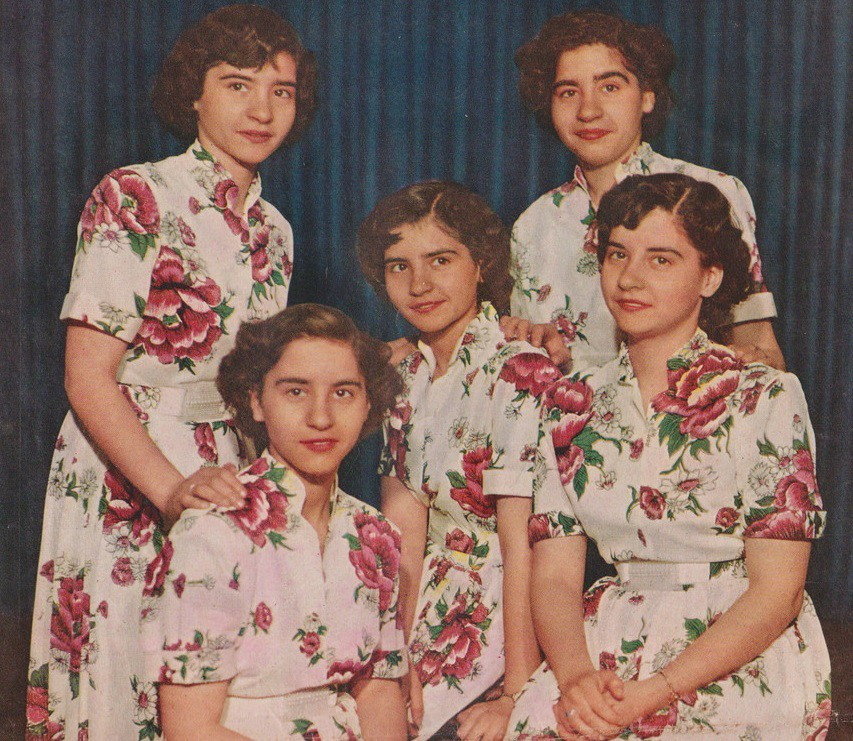 The Dionne Quintuplets looking alike wearing identical flowered dresses