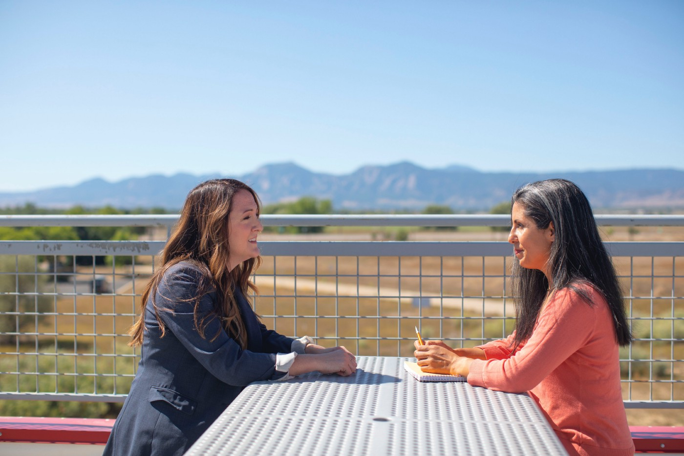 Two women are sitting outside and talking. They are sitting at a metal table and they seem to be having a business meeting. There is a view of nearby hills. It's a sunny day.